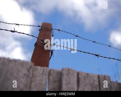 Steel barb wire on a fence under cloudy sky, Australia 2016 - Stock Photo