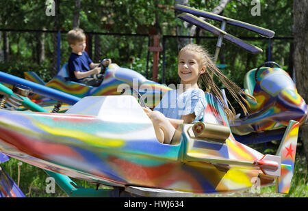Children, sister and brother ride on a toy airplane - an attraction in the park - Stock Photo