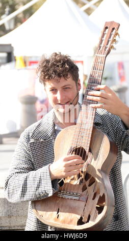 male busker playing guitar and singing