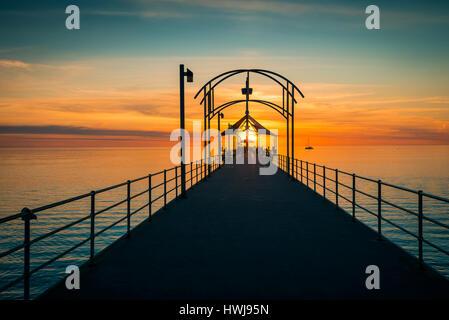 Adelaide, Australia - October 2, 2015: People walking along Brighton Jetty at sunset - Stock Photo