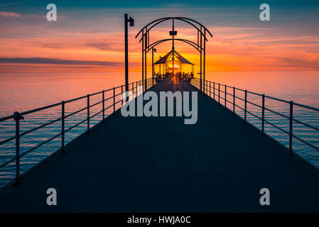 People walking along Brighton Jetty at sunset - Stock Photo
