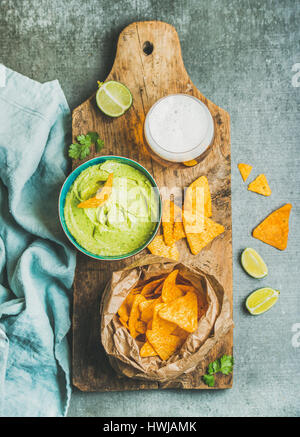 Mexican corn chips, fresh guacamole sauce in blue bowl and glass of wheat beer on rustic wooden serving board over - Stock Photo