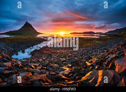 The picturesque sunset over landscapes and waterfalls. Kirkjufell mountain. Iceland - Stock Photo