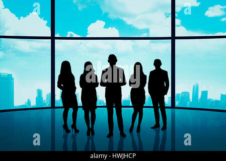 Business team standing against window with cityscape background - Stock Photo