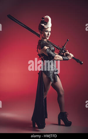 Beautiful warrior woman. Fantasy fighter. Princess or queen in leather corset ready for war. Red light and white weapon. Stock Photo