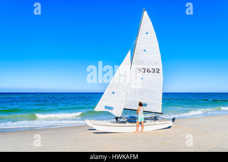 SYLT ISLAND, GERMANY - SEP 9, 2016: young woman standing near sailing boat on Kampen beach, Sylt island, Germany. - Stock Photo
