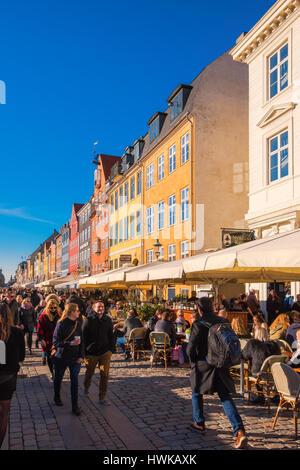 COPENHAGEN, DENMARK - MARCH 11, 2017: Tourists in Copenhagen Nyhavn district promenade with its colorful facades, - Stock Photo