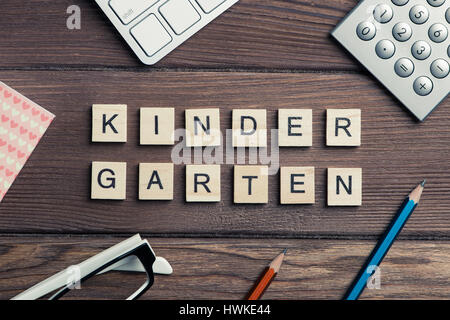 Office stuff and Kinder Garden phrase collected with letters on  - Stock Photo