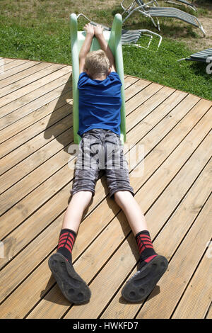 Boy 7 Laying On Deck In Bare Feet Stock Photo Royalty