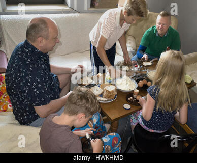 Polish breakfast of three generations with grandfather, father and children eating  eggs, bread, butter, and cottage - Stock Photo