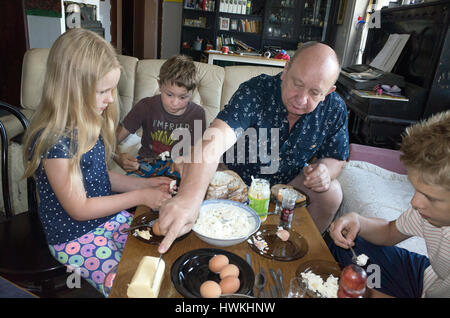 Breakfast in Poland, grandfather 58, granddaughter 8, grandsons 10 and 12 with eggs, bread, and cheese. Zawady Central - Stock Photo