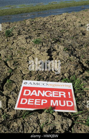 Warning sign - deep mud after dredging of river - Stock Photo