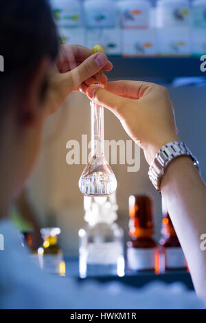 Professional woman, laboratory technician working in a medical lab with round-bottom flask. Medicine, healthcare, - Stock Photo