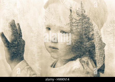 Little boy daydreaming, looking out the window at nature, thinking about it. Double exposure of child portrait and - Stock Photo