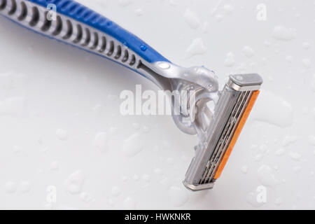 Disposable razor blade close up on white wet background with water drops - Stock Photo