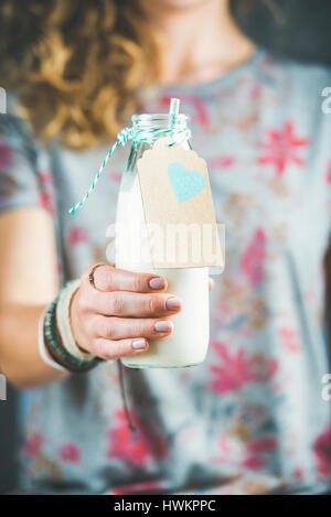 Young blond woman in grey t-shirt with floral pattern holding bottle of dairy-free almond milk in her hand. Clean - Stock Photo