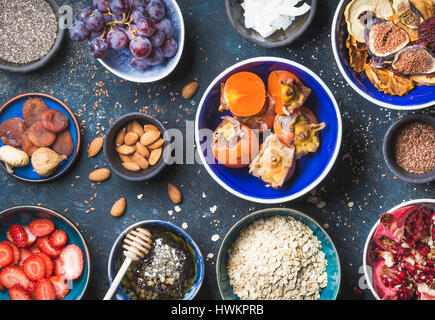 Ingredients in bowls for healthy breakfast over dark blue background, top view. Fresh and dried fruit, chia seeds, - Stock Photo
