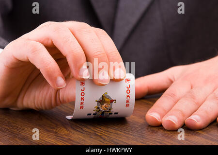Businessman showing joker card. - Stock Photo