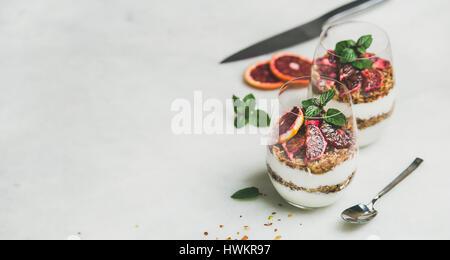 Healthy breakfast with greek yogurt, granola, blood orange layered parfait - Stock Photo