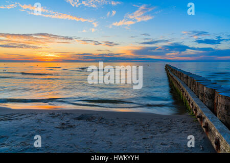 Sunset over sea with wooden breakwaters in foreground on Leba beach, Baltic Sea, Poland - Stock Photo