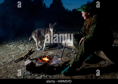 Woman with her dog around campfire at night forest - Stock Photo