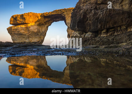 Gozo, Malta - Sunriseat the beautiful Azure Window, a natural arch and famous landmark on the island of Gozo with - Stock Photo
