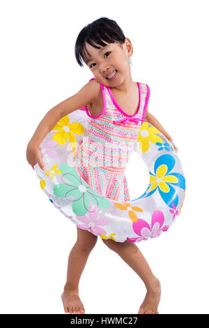 Asian Chinese little girl portrait wearing swimsuit with swim ring in isolated white background. - Stock Photo