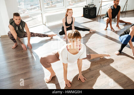 Group of concentrated young people stretching and practicing yoga in studio - Stock Photo
