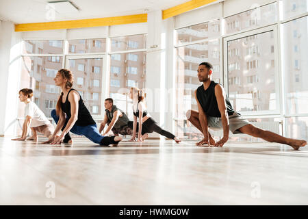 Multiethnic group of young people practicing yoga in studio together - Stock Photo