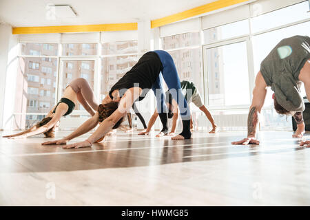 Group of people standing and practicing yoga in studio - Stock Photo