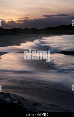 Couple walking along beach on Isle of Harris - Stock Photo