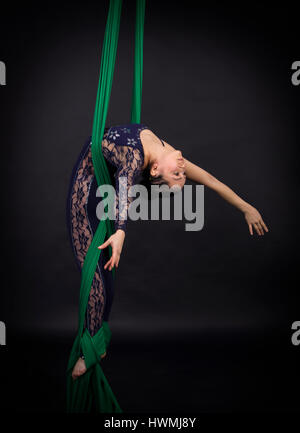 Girl's aerial acrobatics in the paintings - dark background. Studio photography of circus performers - Stock Photo