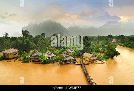 Vang Vieng Laos landmark the hut village with the wooden brigde in cloudy and morning low lighthing - Stock Photo