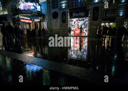night view of people and reflections on wet street in piccadilly circus - Stock Photo