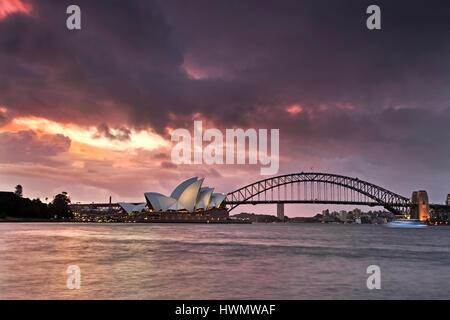 Sydney, Australia - 19 March 2017: Sydney opera house and Harbour bridge during stormy weather and orange sunset - Stock Photo