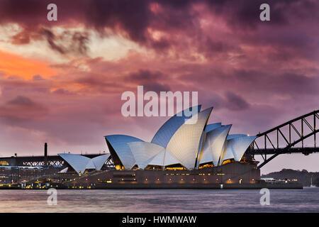 Sydney, Australia - 19 March 2017: Colourful sunset through thick clouds over world famous landmark - Sydney Opera - Stock Photo