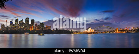 Sunset over Sydney harbour from tall skyscrapers to Harbour bridge, North Sydney and other architectural landmarks - Stock Photo