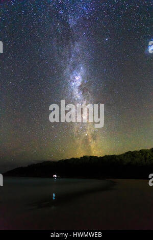 Stargazing of southern sky at empty sandy beach on a calm cloudless night seeing milky way and southern cross constellation. - Stock Photo