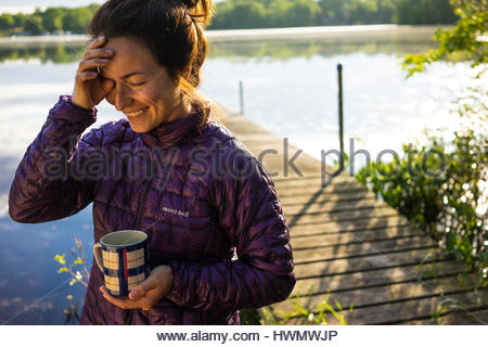 A young lady wipes sleep out of her eyes while holding a coffee cup on a lake front dock. - Stock Photo