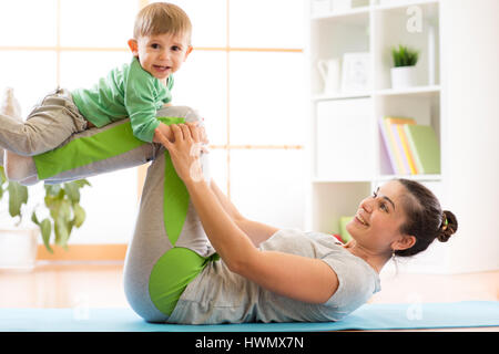 family mother and kid son are engaged in meditation and yoga, exercising at home