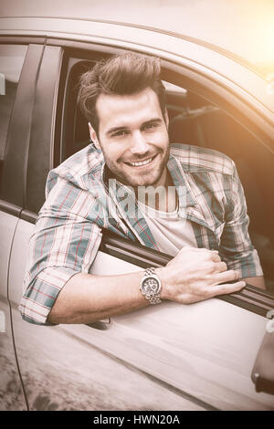 Portrait of young smiling man sitting in his car - Stock Photo