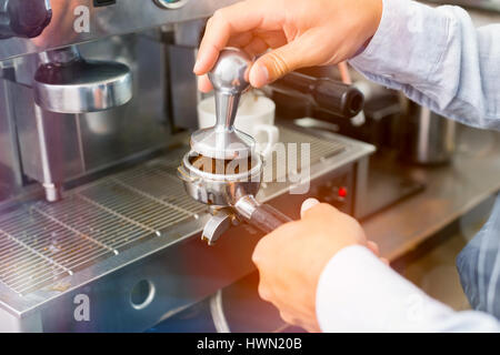 Graphic image of flare against cropped hands of barista making cup of coffee - Stock Photo