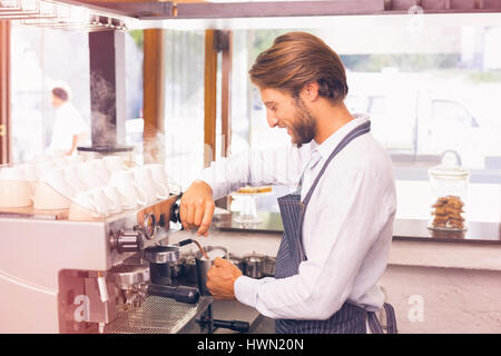 Graphic image of flare against handsome barista making coffee - Stock Photo