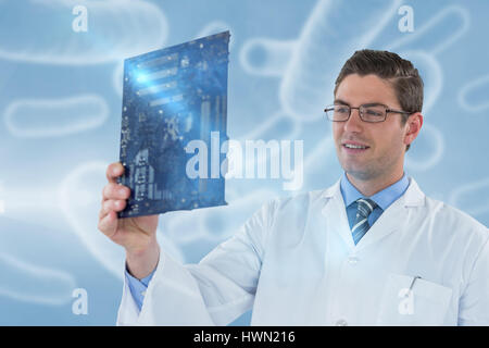 Computer engineer holding motherboard against digital image of red bacteria 3d - Stock Photo