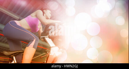 Low angle view of a determined young woman working out at spinning class in gym - Stock Photo
