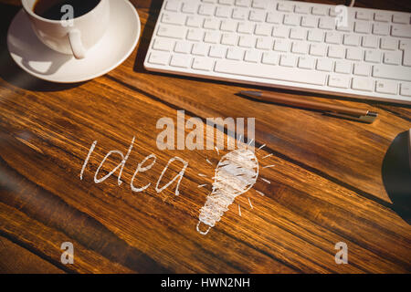 Close-up of glowing bulb against view of a desk - Stock Photo