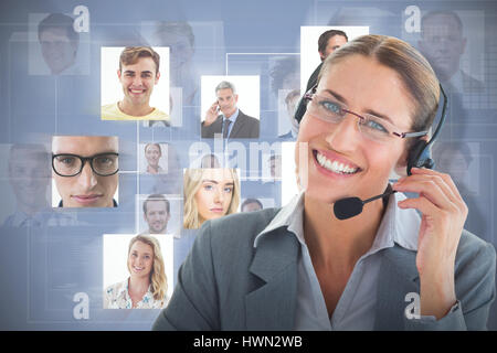 Portrait of a call center executive wearing headset against grey background - Stock Photo