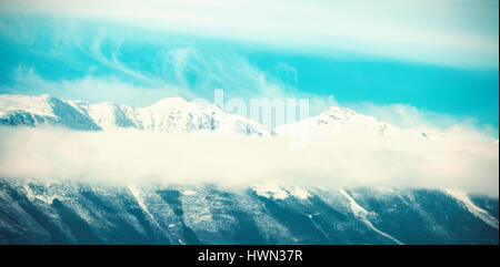 Scenic view of snowy mountain range against blue sky - Stock Photo