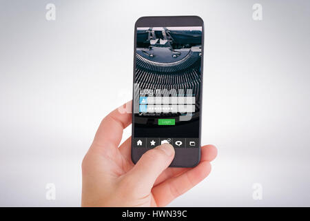 Female hand holding a smartphone against smartphone screen - Stock Photo