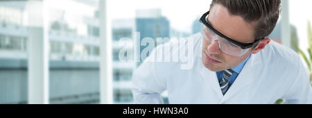 Doctor wearing protective eyewear against laptop on desk by glass window in office - Stock Photo